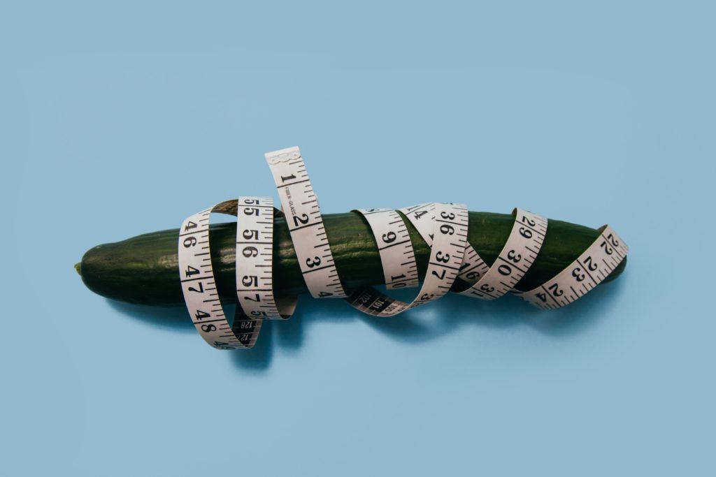 un concombre enlacé par mètre à ruban qui signifient la cironférence du pénis