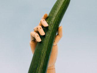 une main de figurine tennante un comcombre en imitant jelqing