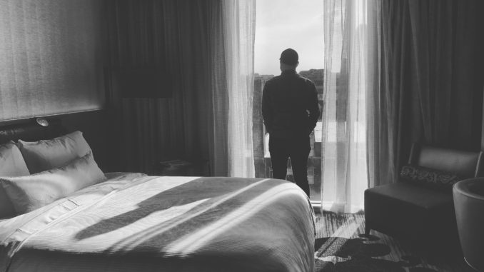 un homme débout dans la porte triste car il souffre des troubles de l'érection