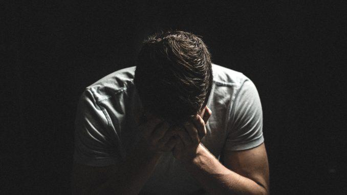 un homme ayant sa tete dans ses mains a cause des problemes avec l'érection faibles